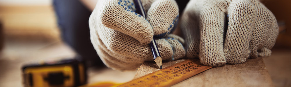 Close-up of craftsman hands in protective gloves measuring wood